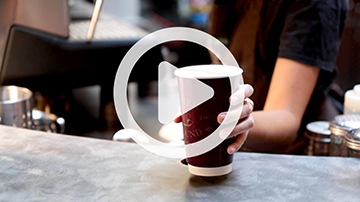 Person grabbing a coffee cup off of counter